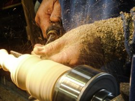 Spindle woodturning demonstration on a lathe showing chips flying from a chisel
