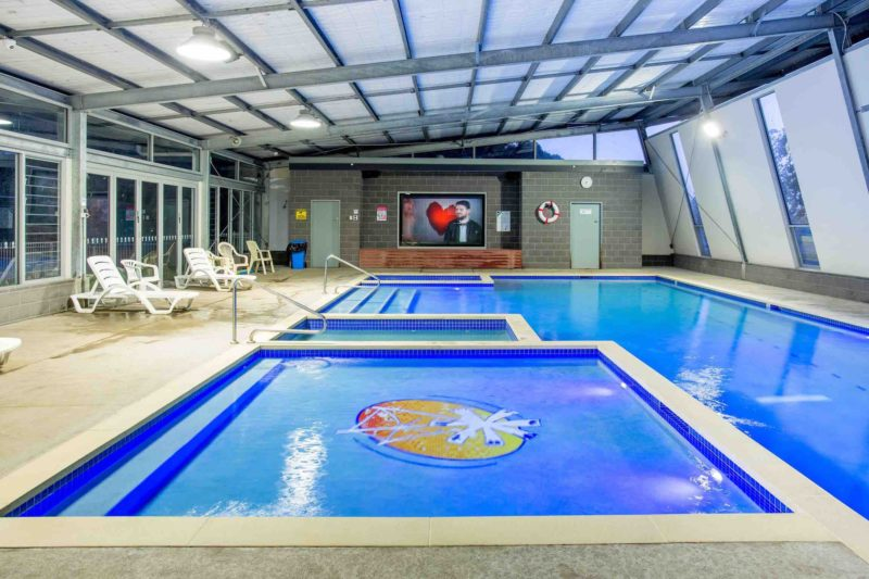 Indoor heated pool complex with giant TV screen