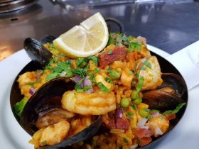 Paella dish with prawns, mussels, chorizo and fresh lemon wedge