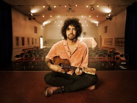 Bobby Alu, sitting on a stage with a Ukelele in his hand, back facing the empty theatre.