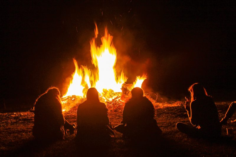 Four people sitting in front of bonfire