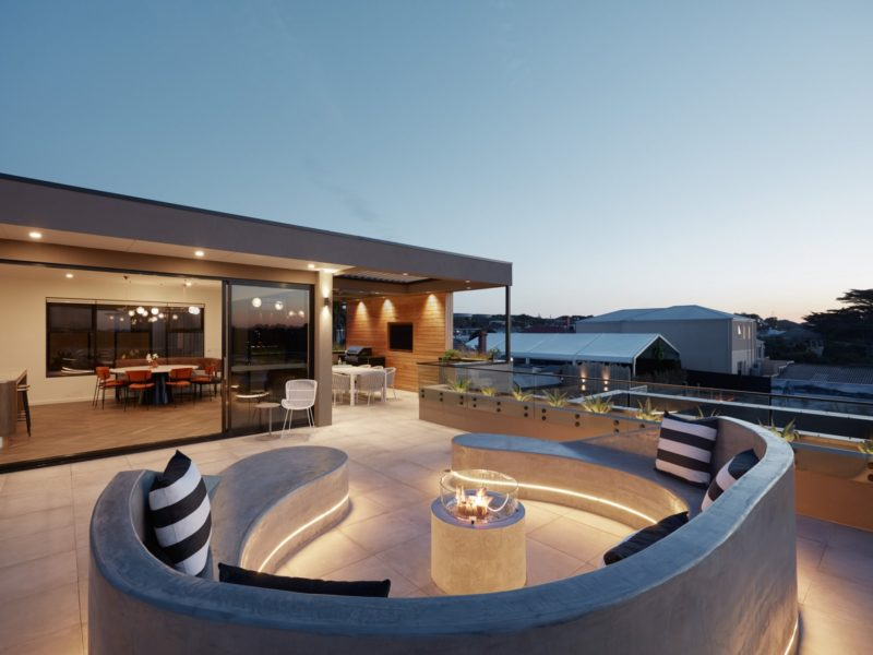Luxury Exclusive Penthouse balcony entertaining area with seating and fireplace