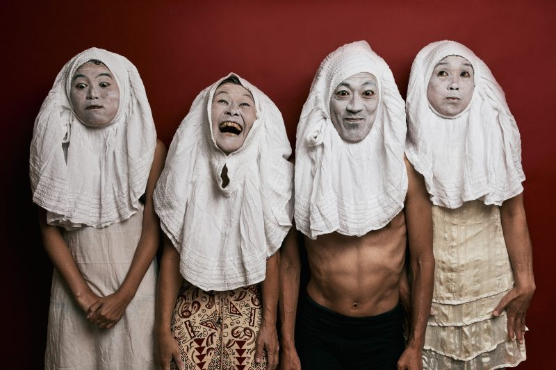 Four performers posing with white paint on tehir faces