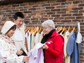 Chinese couple looking at historic costumes and wearing costumes with Cooks' Cottage volunteer