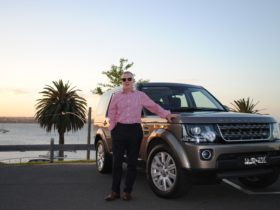 Ross standing next to his 2016 Land Rover Discovery.