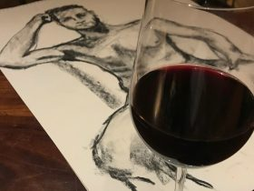 Image of charcoal life drawing and wine glass.
