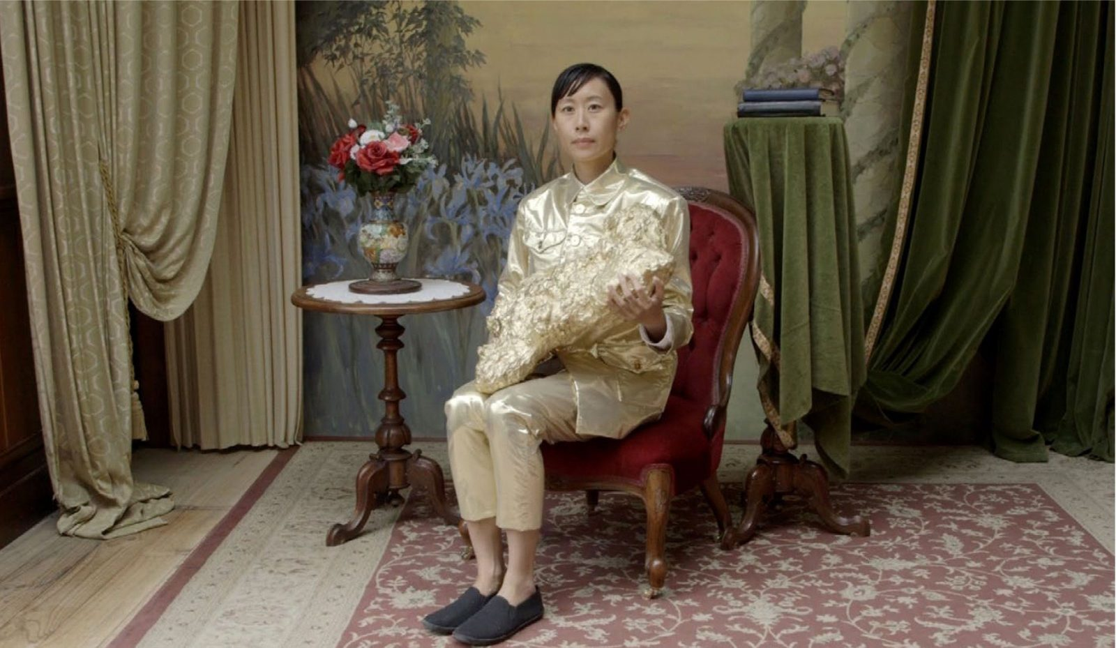 The Ambassador in gold suit sitting in old photography studio