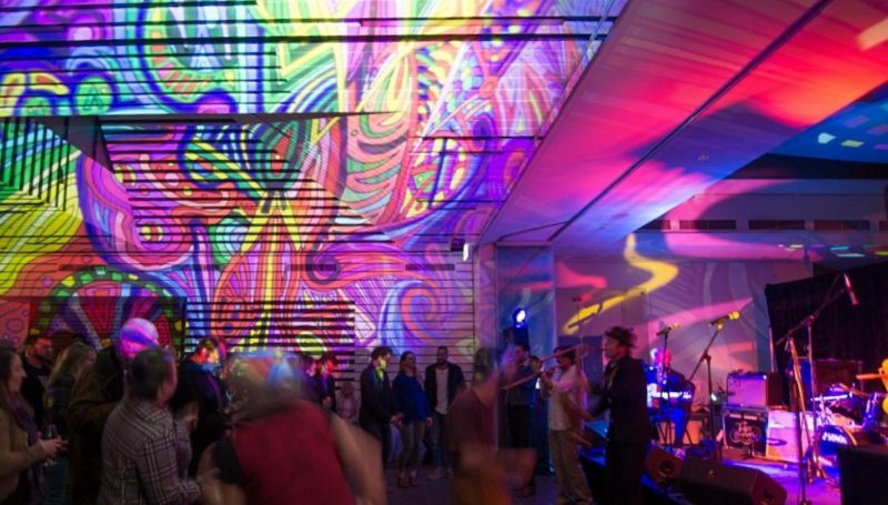 Live music performance in front of audience, light murals on building walls and ceiling