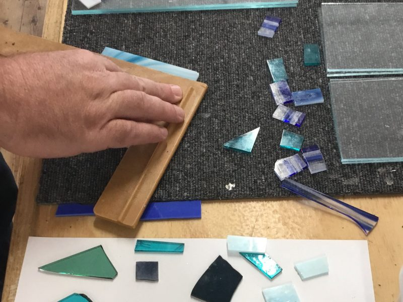 Student hands working on a fused glass platter