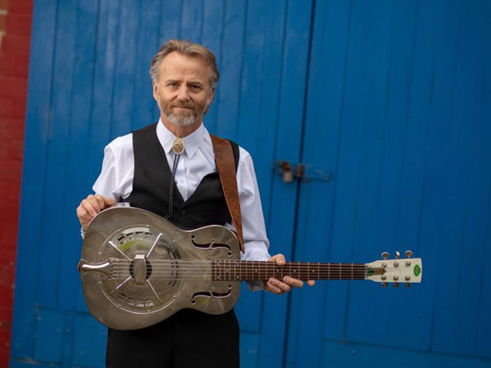 Geoff Achison standing in front of a blue door holding a dobbero guitar