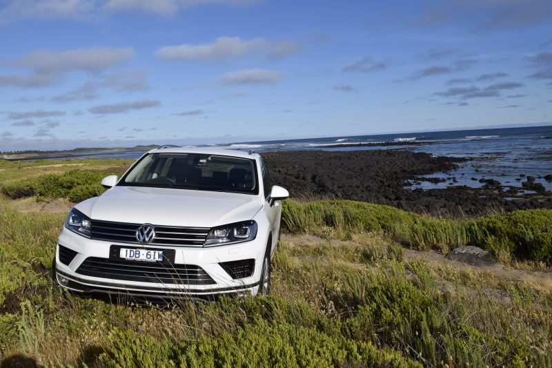 White VW Touareg SUV wagon in foreground of rocky shore and ocean