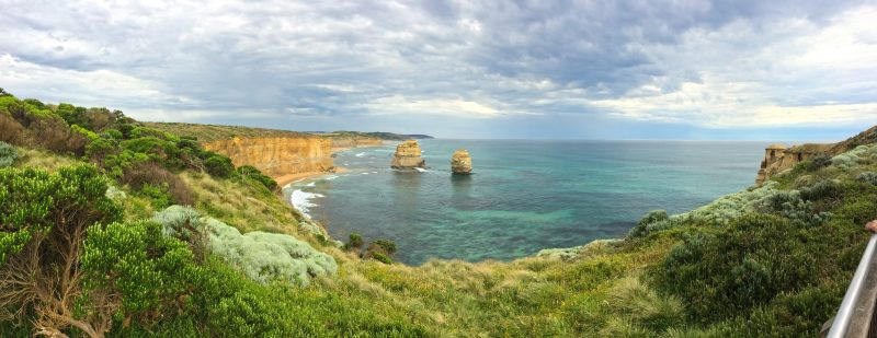 12 Apostles, cliffs and clear ocean viewed across green foreground in midday light