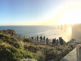 Late afternoon sun over the ocean at the 12 Apostles, watches by people on the viewing platform