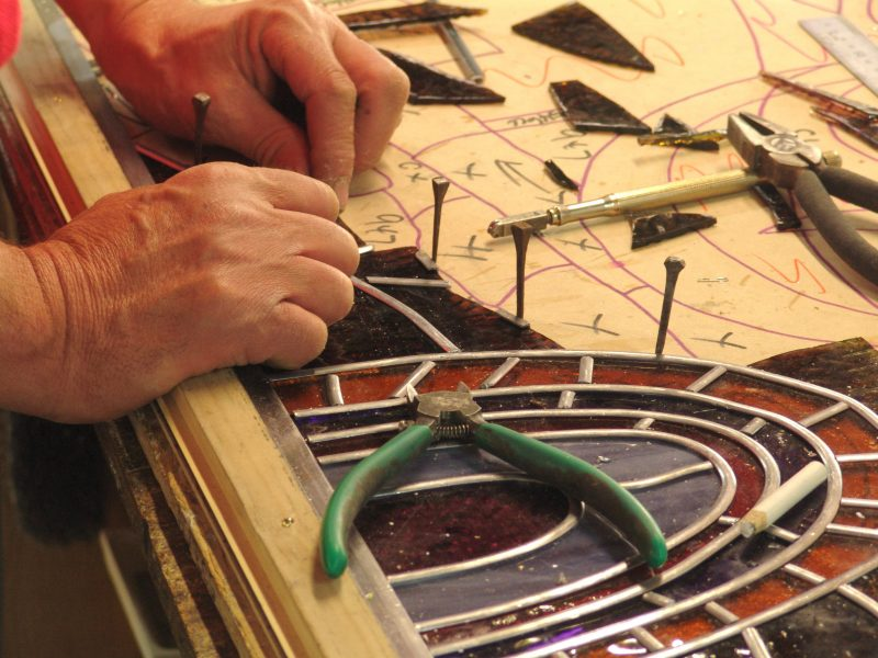 Set of hands working on a leadlight panel. Traditional skill