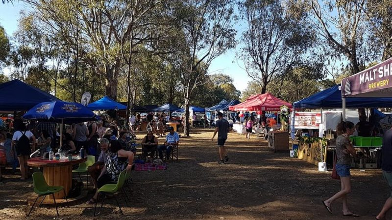 Craft beer, wine and cider vendors setup under the gums patrons tasting and listening to live music
