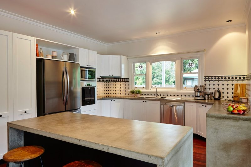 Modern country style kitchen with concrete benches and modern appliances and french door fridge
