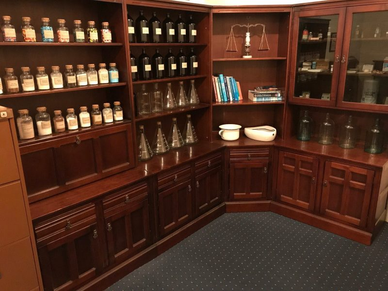 Photo of replica pharmacy shelving with pills, powders and potions.