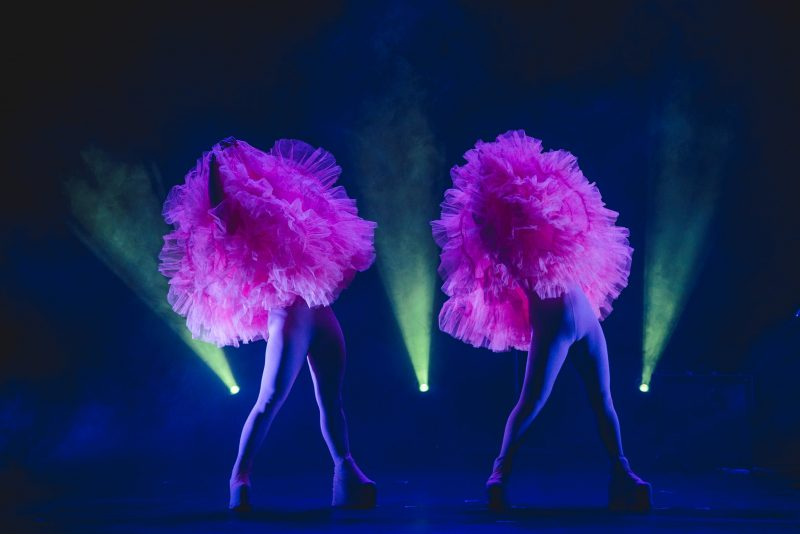 Two performers holding pink tutu on a dark stage