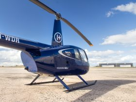 Blue Robinson R44 Cadet helicopter parked at the airport.