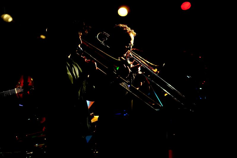Two musicians play trombones in a dark jazz club, lit by just a few stage lights