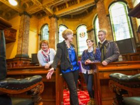 A Town Hall tour guide showing visitors inside The Council Chamber