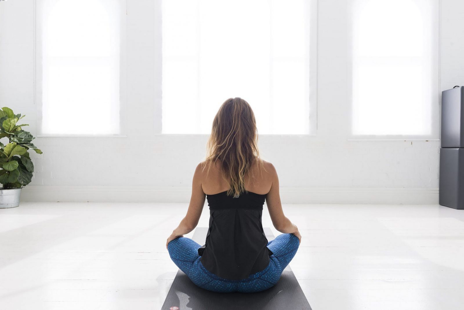 person sitting calmly in brightly lit yoga studio