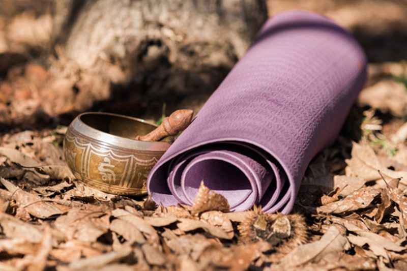 Purple yoga mat and ringing bowl in autumn leaves