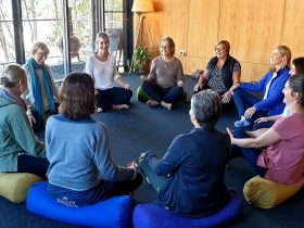 Emily Rose seated with attendees, forming a circle, welcoming everyone to retreat
