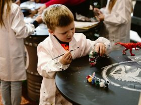 Young boy painting 3D dinosaur
