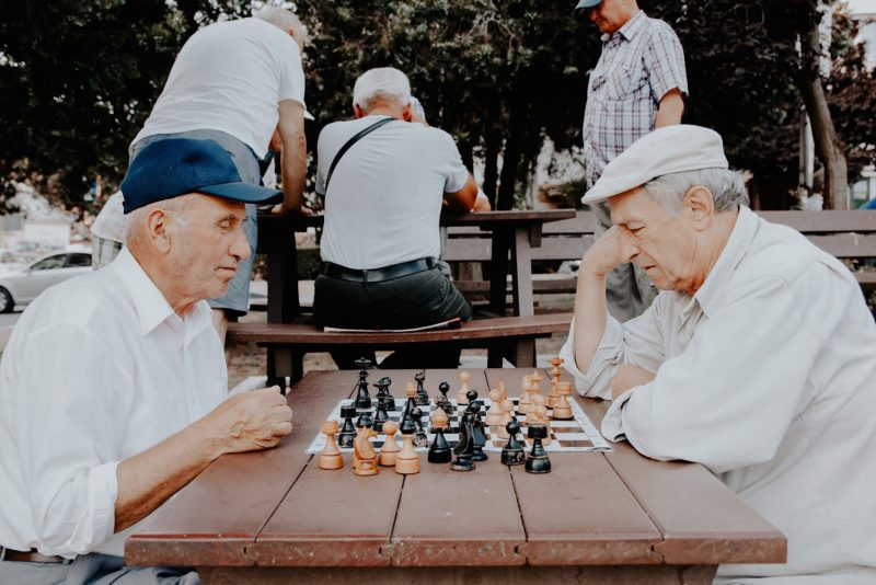 Two older people playing chess in the park