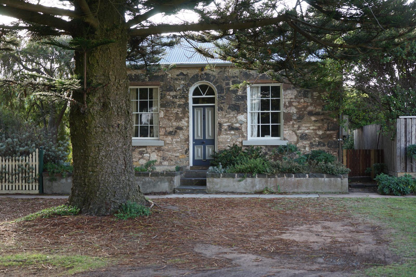 Historic stone cottage nestled under the giant Norfolk pies