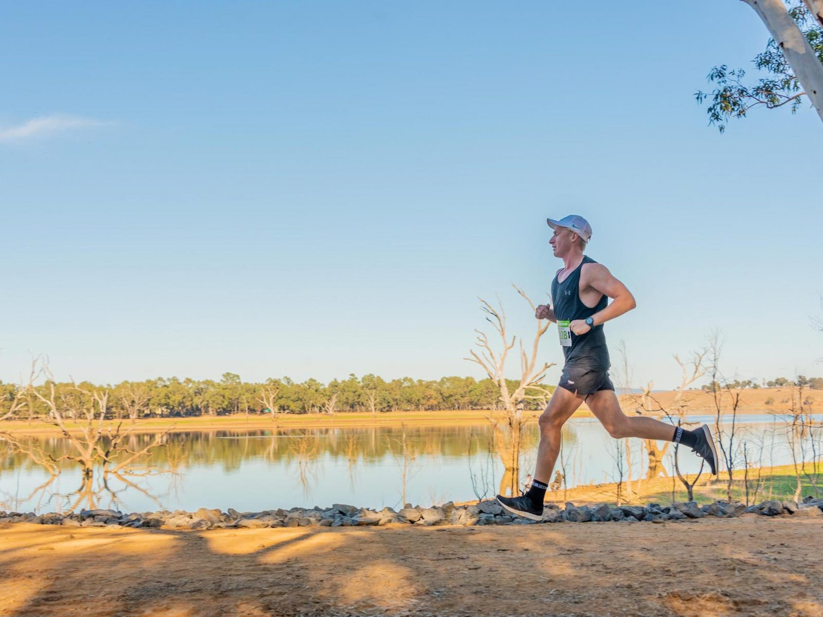 Male runner running past Lake Eppalock in the O'Keefe Challenge