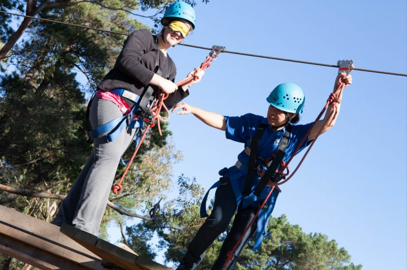image: blindfolded girl supported by People Outodors volunteer on high ropes course