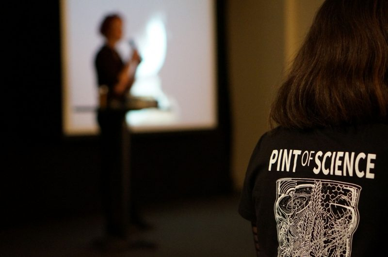 Scientist talking with camera focus on Pint of Science t-shirt