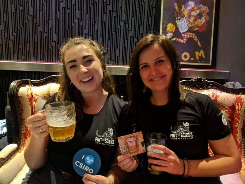 Volunteers drinking beer and holding up PoS coaster