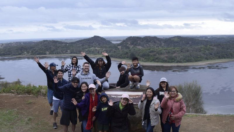 Happy people at Von Guerard lookout with Tower Hill crater lake and nested hills in background