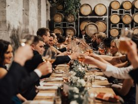 People sitting at a feasting style table. making a toast