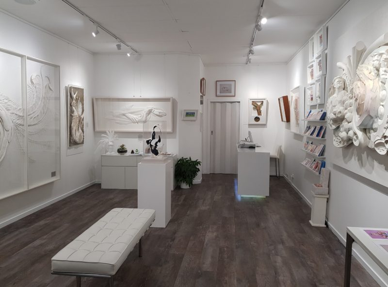 Looking into the Gallery showing artworks on all walls and freestanding plinth based sculpture