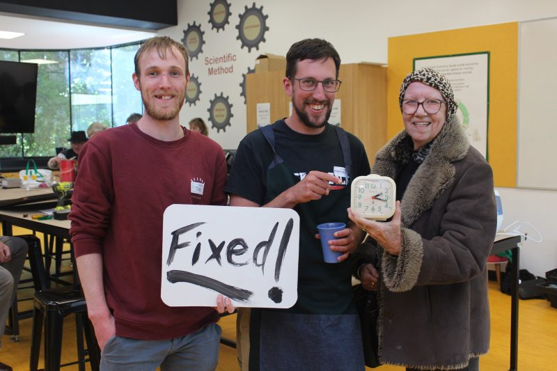 Volunteers work with a visitor to fix their clock.