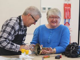 A volunteer works with a visitor to fix their antique clock.