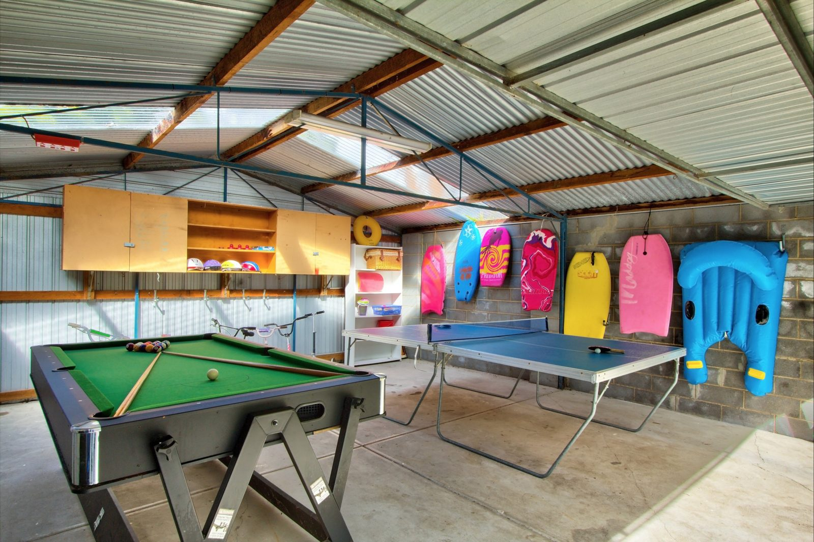 Outdoor games room with pool table, air hockey, table tennis, little bikes and scooters.