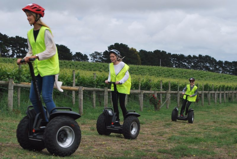 Three riders on Segways with the vines in the background