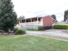 Sunflower Cottage. Front verandah looking onto expansive gardens/lawn and across to paddocks.