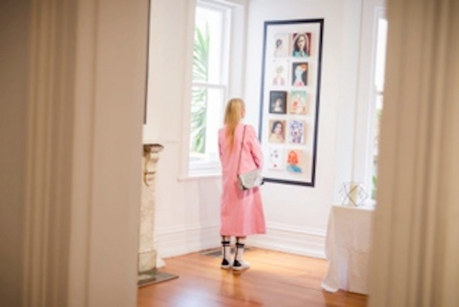 Woman in gallery looking at postcards on a wall