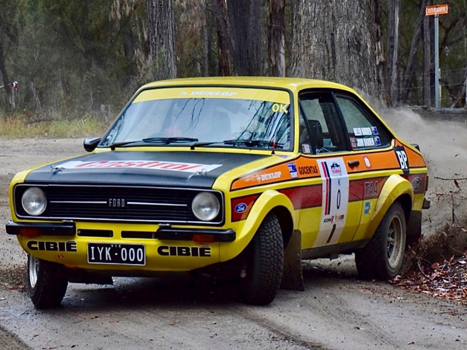 A yellow Ford Escort rally car driving through a forest at high speed