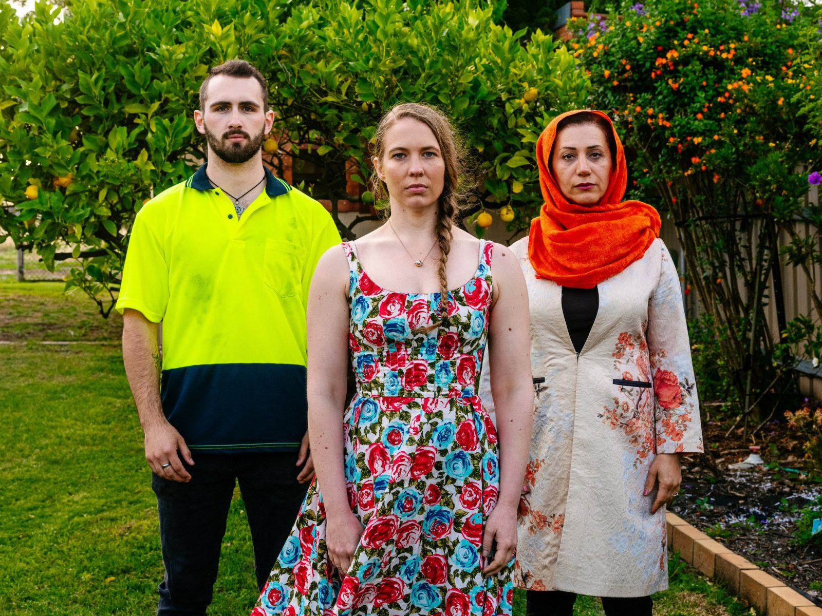 A portrait of man in a high vis shirt, a woman in a floral dress and a woman in an orange headscarf