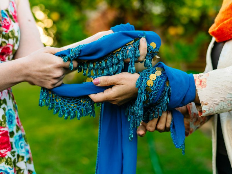 A blue belly dancing coin belt twisted between two women's hands