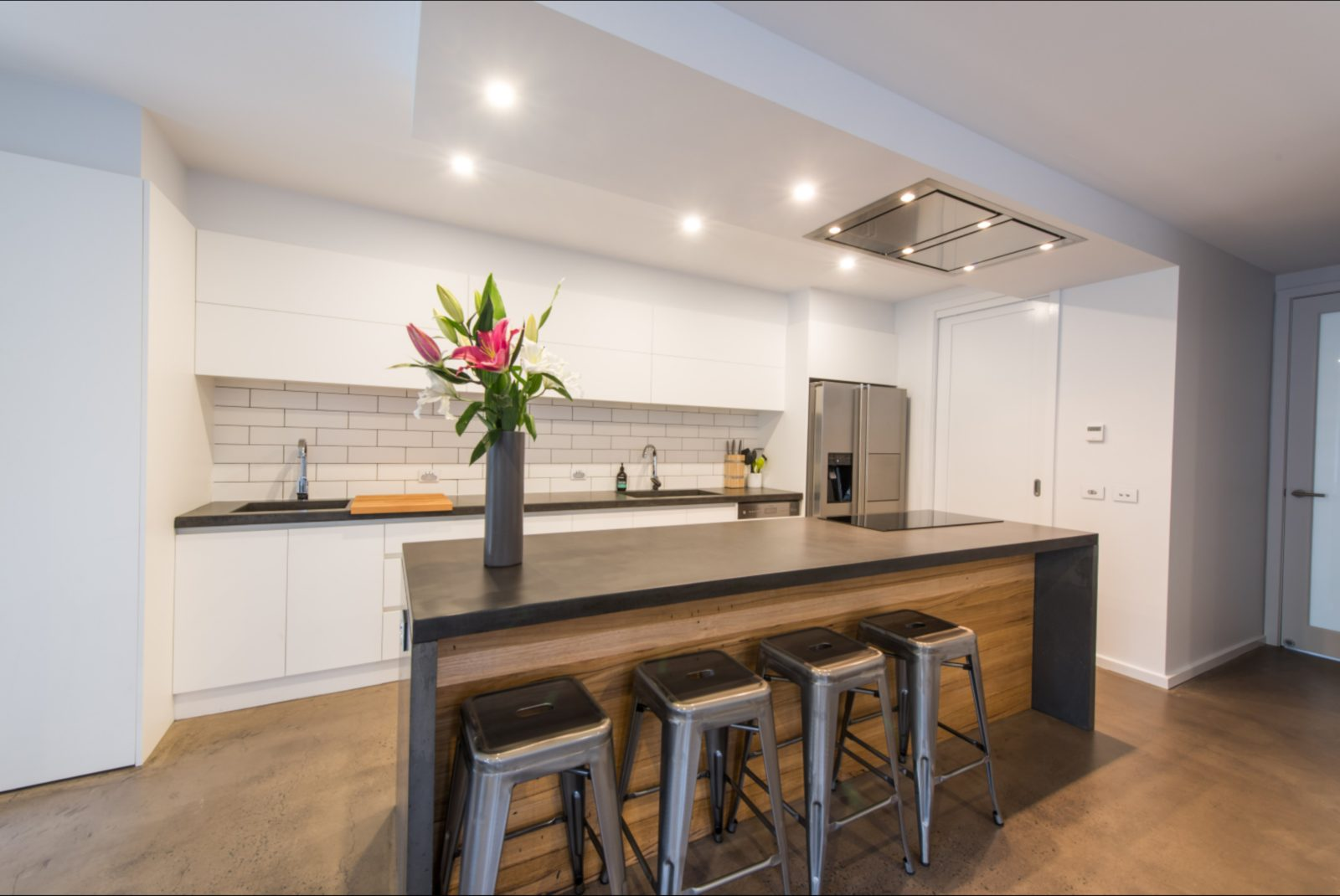 Fully equipped kitchen with custom made concrete island bench, four stools at breakfast bar.