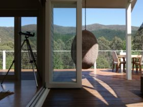 View from deck of hanging pod chair, telescope, outdoor table and mountain