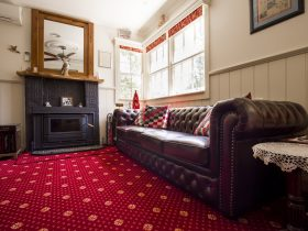 Loung area with slow combustion wood fireplace and Chesterfield lounge.